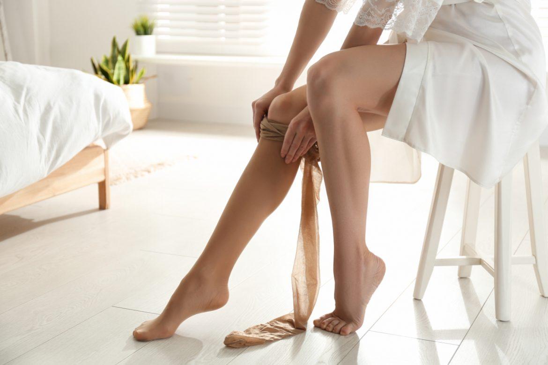 Jak dobrać rajstopy przeciwżylakowe i pończochy uciskowe na żylaki? Kobieta wkłada na nogę rajstopy, siedząc na krześle w sypialni.