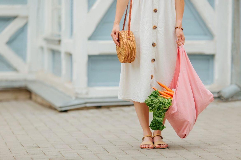 Jak być eko? Jak żyć ekologicznie? Kobieta w białej sukience i sandałach, z wiklinową torebką wiszącą na ramieniu stoi na tle białego budynku i trzyma w ręku różową materiałową torbę na zakupy z warzywami w środku.