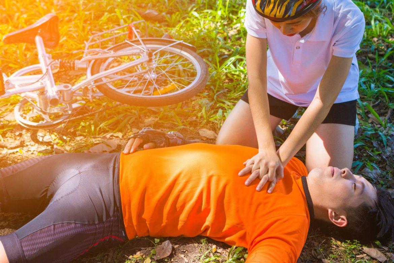 Jak powinna przebiegać resuscytacja? Kobieta resuscytuje rowerzystę.