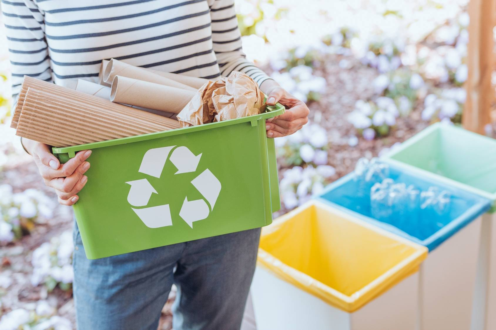 Czym zastąpić plastik - alternatywy dla plastiku? Kobieta trzyma pojemnik do recyklingu i segreguje śmieci.