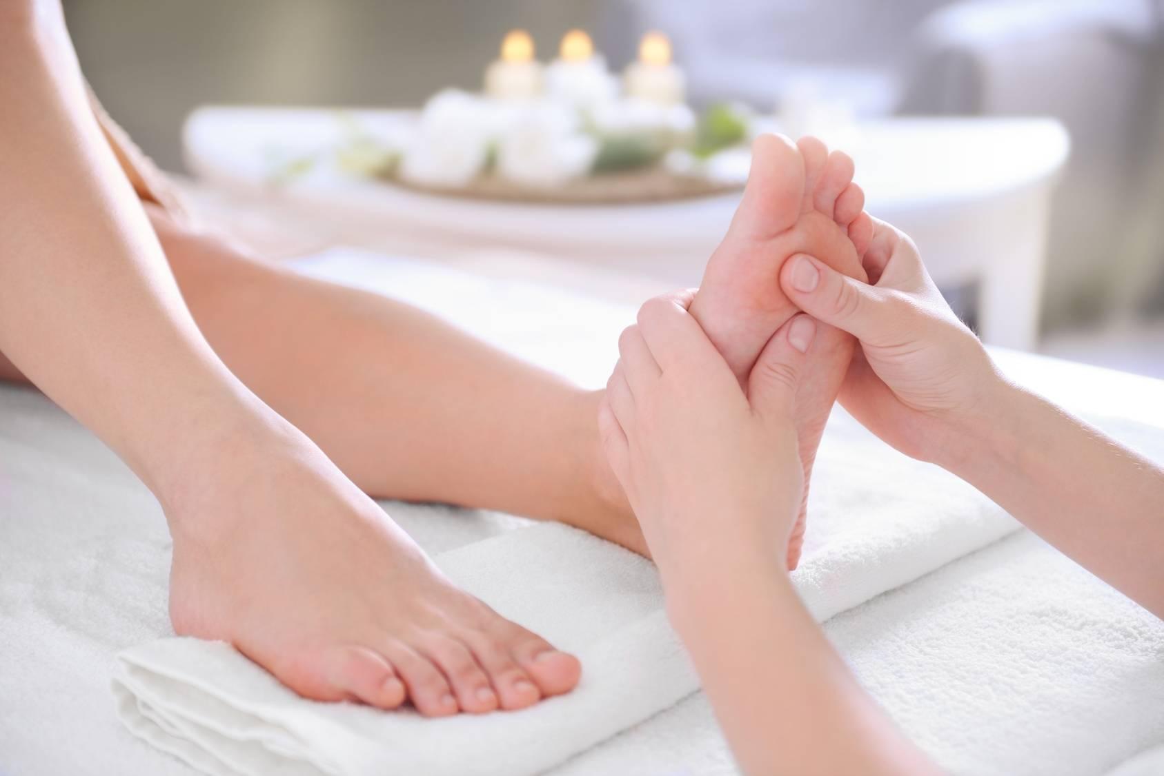 Refleksologia - na czym polega leczniczy masaż stóp? Jak wygląda zabieg refleksoterapii? Refleksolog wykonuje zabieg w swoim gabinecie - zbliżenie na stopy.