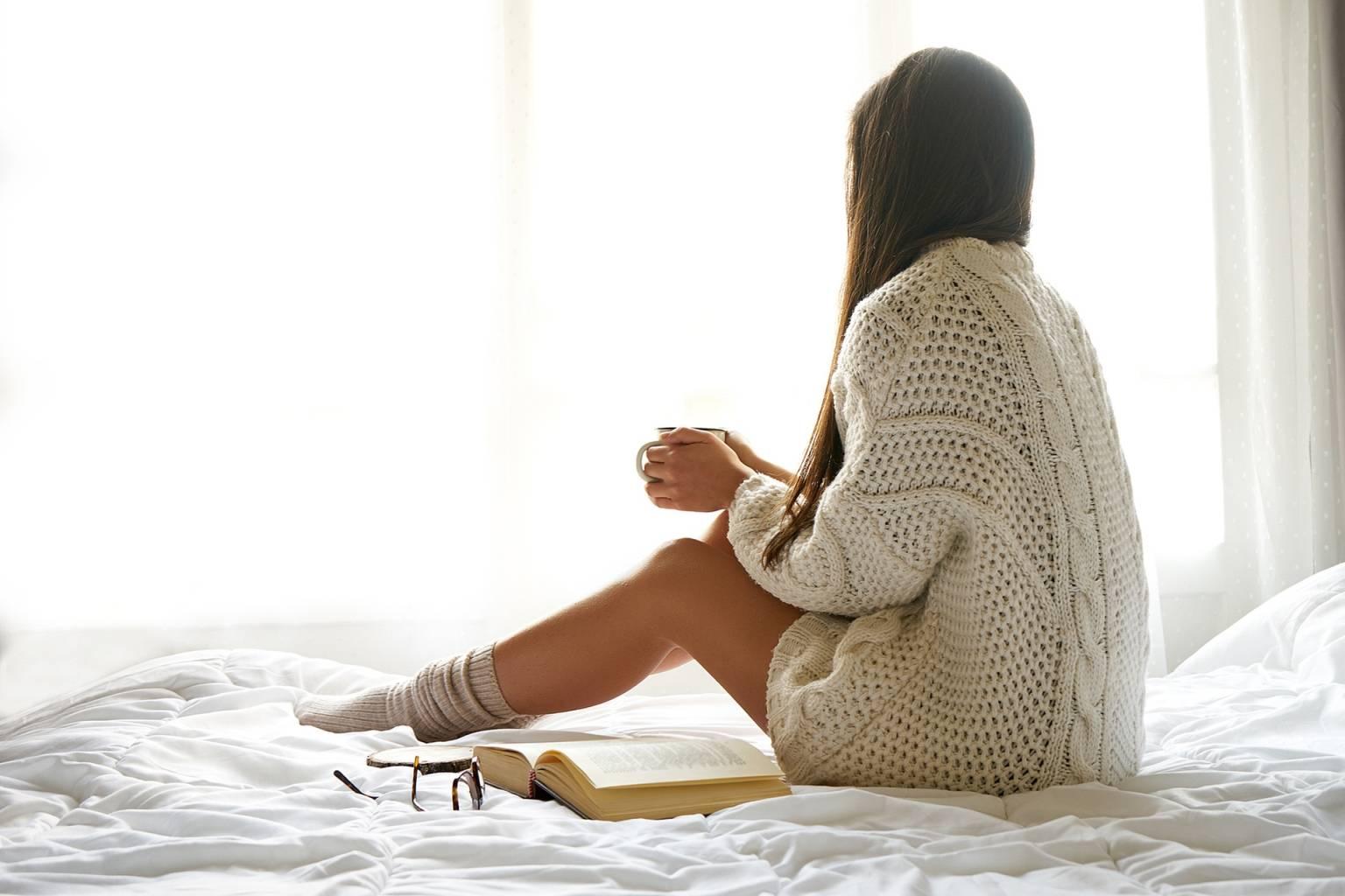 Atak zimnego wiatru w medycynie chińskiej, czyli jak leczyć przeziębienie? Kobieta ubrana w ciepły sweter i skarpetki siedzi z kubkiem herbaty na łóżku, tyłem do aparatu i patrzy w okno, obok leży otwarta książka i okulary.
