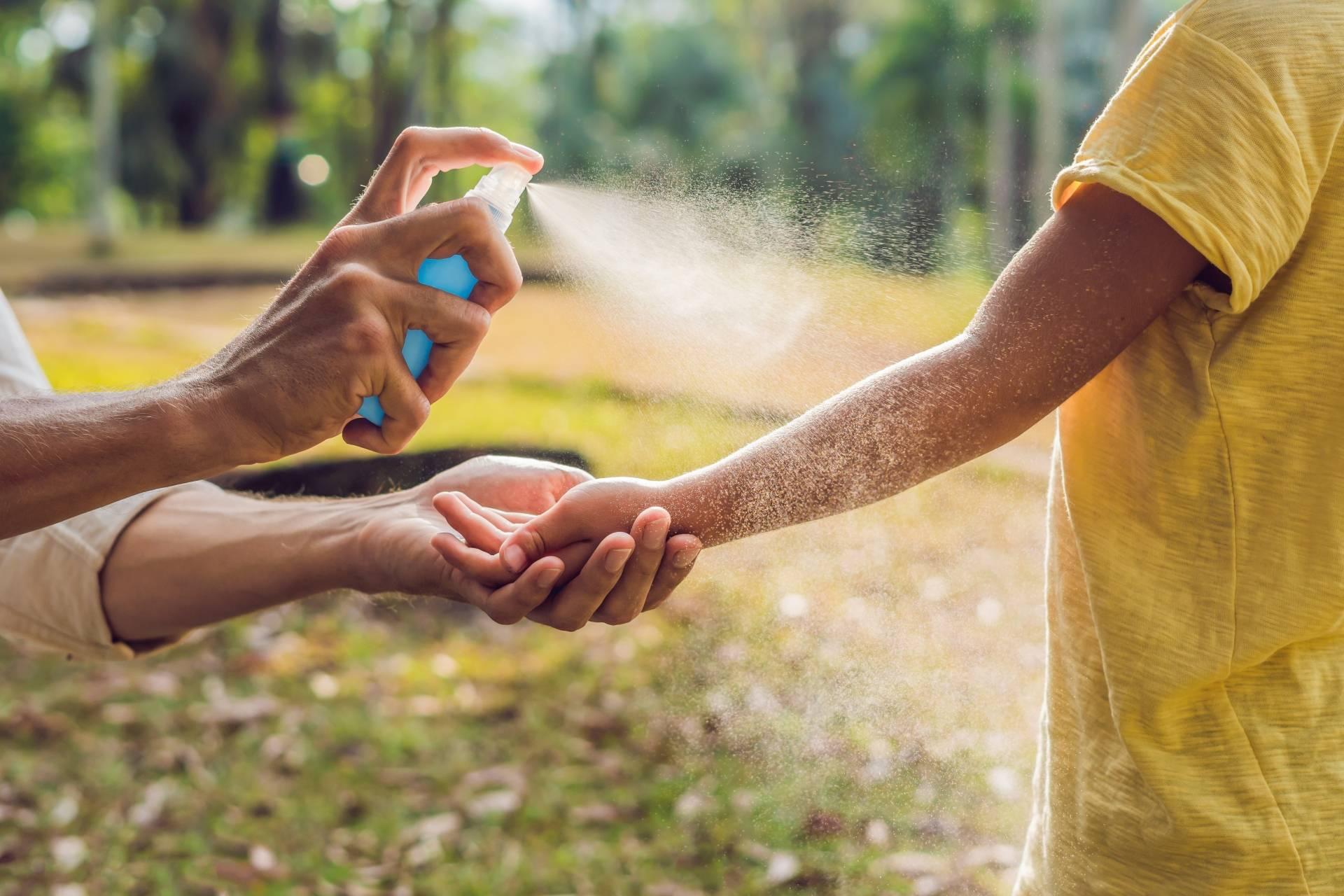 Domowe i naturalne sposoby na komary, kleszcze i inne owady. Jak zrobić domowy spray na komary? Ojciec pryska środek na komary na rękę dziecka.