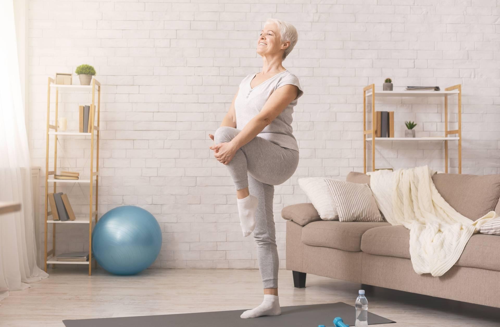 Reumatyzm - objawy i leczenie. Aktywna seniorka w stroju sportowym gimnastykuje się na macie w domu, stoi z podniesioną nogą i przyciąga kolano do siebie.