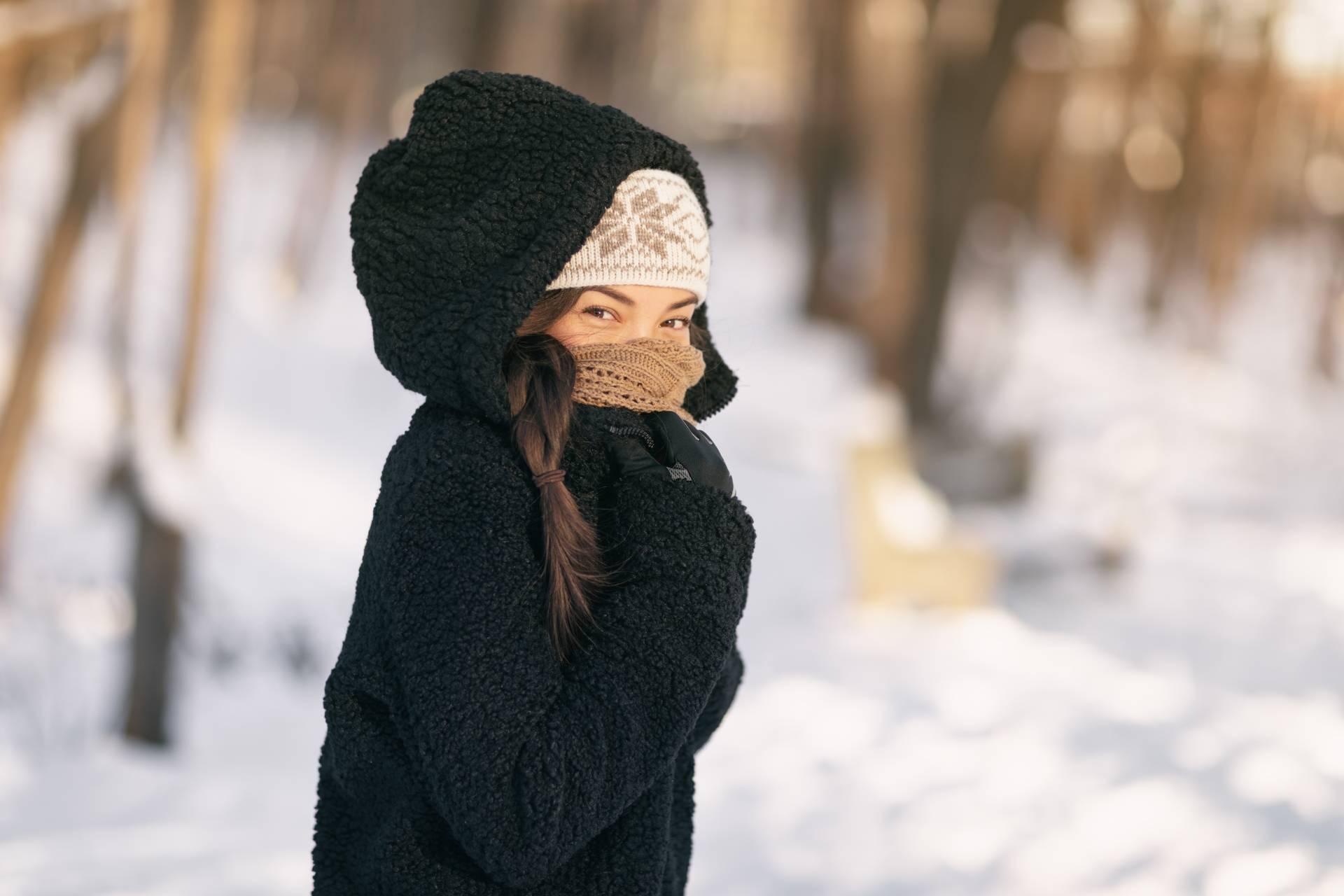 Reumatyzm - jak mu zapobiec? Młoda dziewczyna stoi w lesie opatulona w czarną kurtkę zimową z kapturem, jasną czapkę i ciepły szalik i rękawiczki. z tyłu leży śnieg.