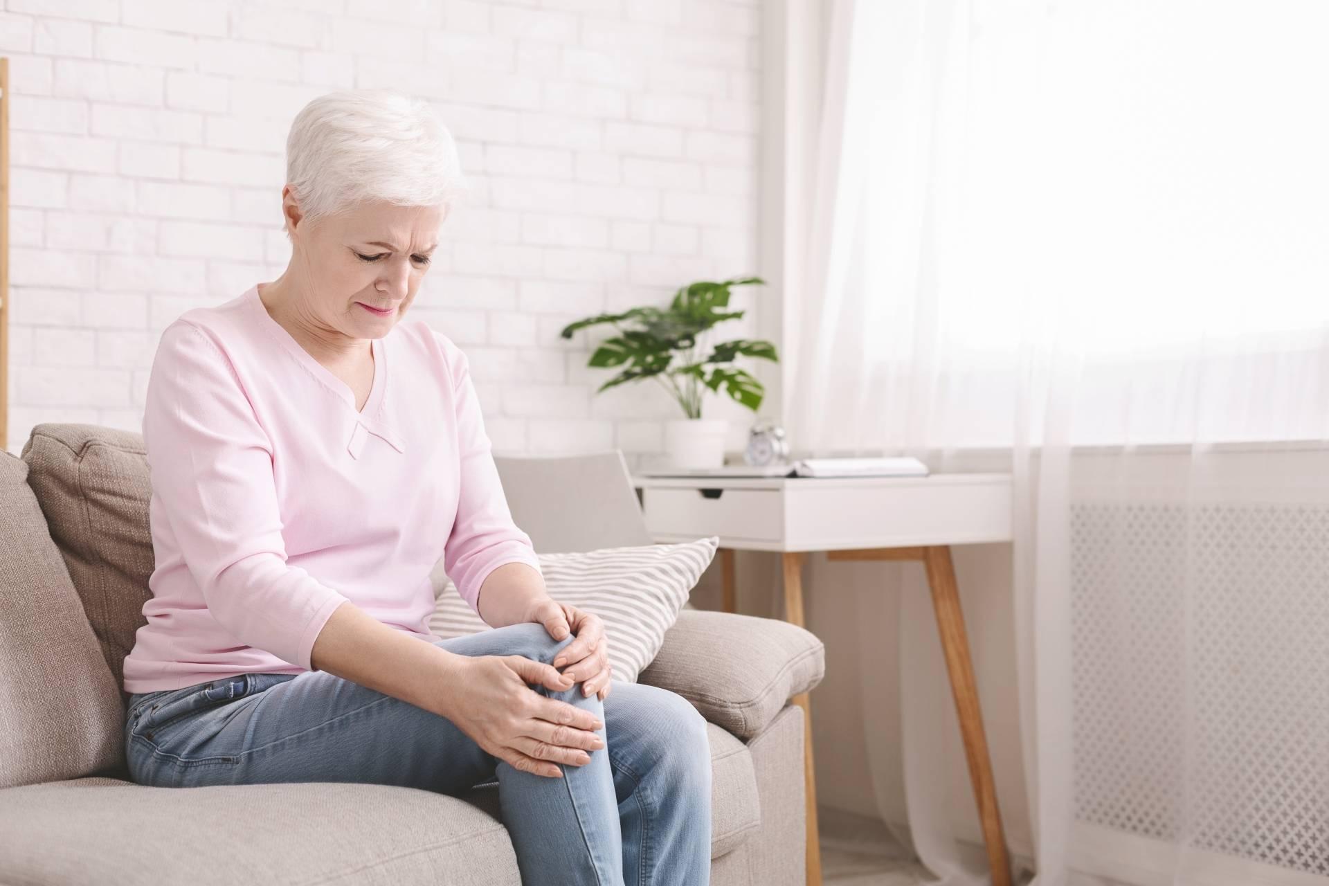 Reumatyzm i bóle reumatyczne - jak je leczyć? Starsza kobieta, seniorka, ubrana w różowy sweterek i jasnoniebieskie jeansy, siedzi w domu na kanapie i trzyma się za bolące kolano.
