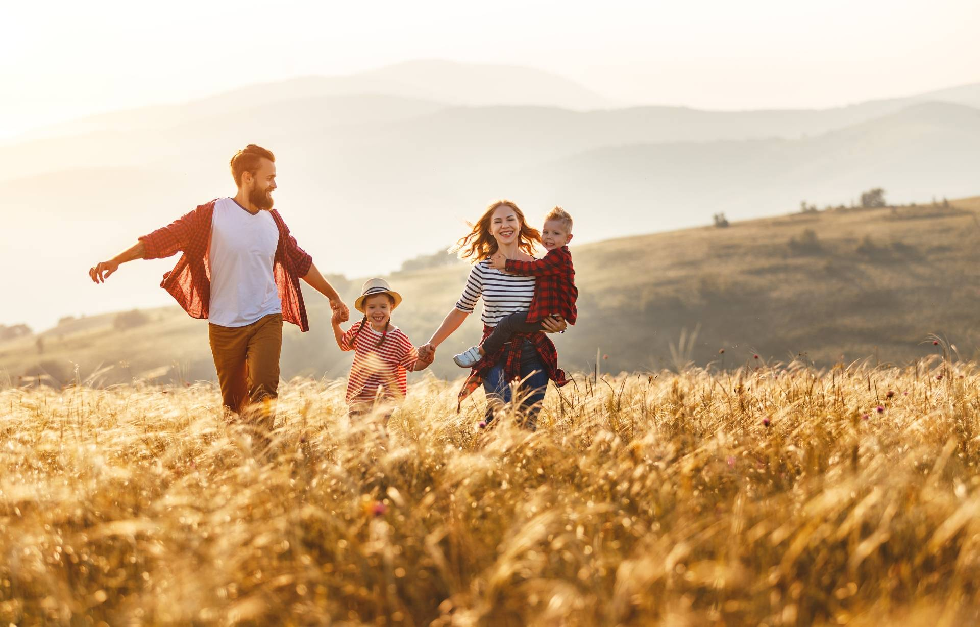 Alergia na pyłki - kiedy warto przeprowadzić odczulanie? Szczęśliwa rodzina - mama, tata i dwoje dzieci - biegną po polu w letnie, słoneczne popołudnie.