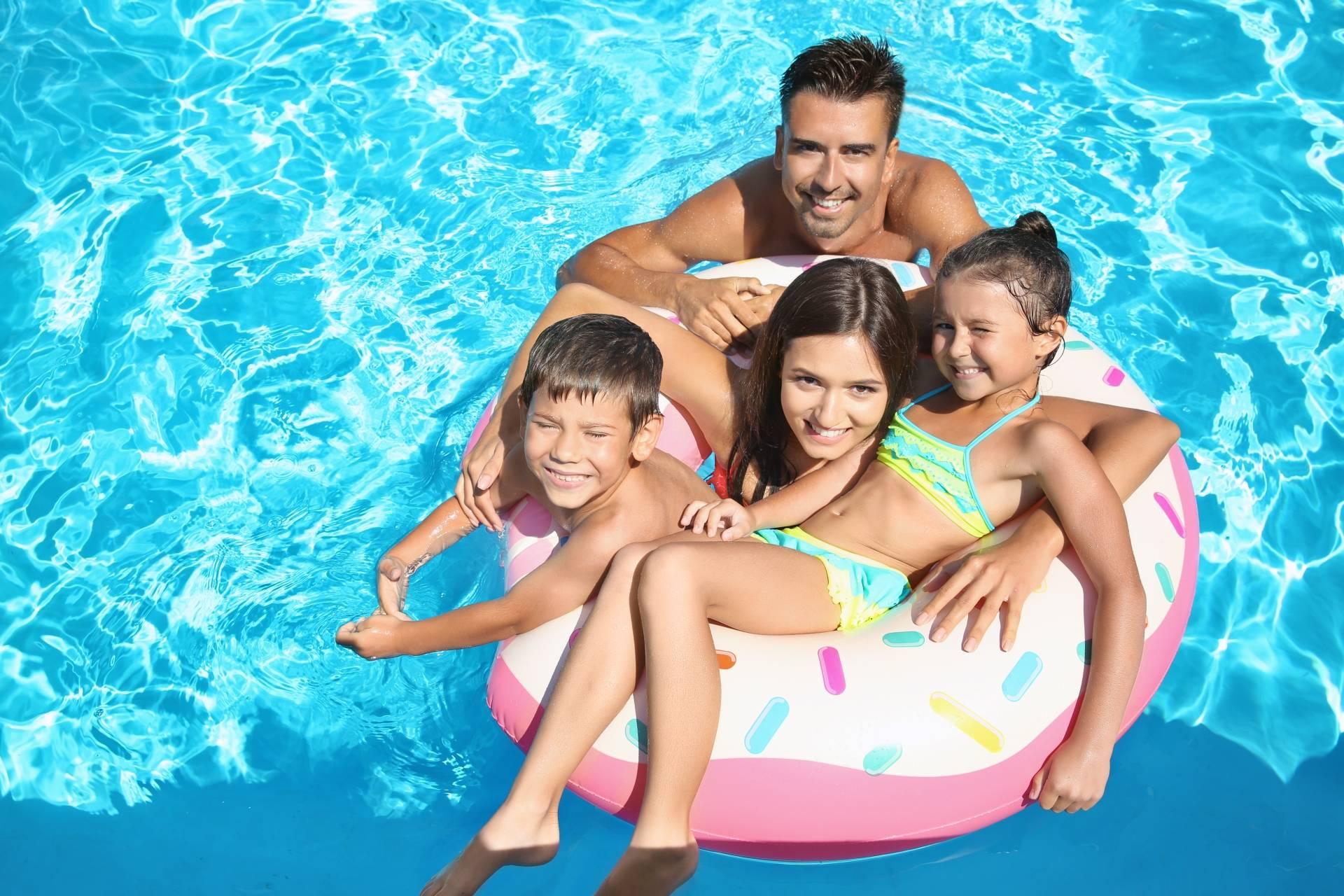 Plamy na skórze - jak ich uniknąć? Szczęśliwa rodzina na pontonie w basenie.