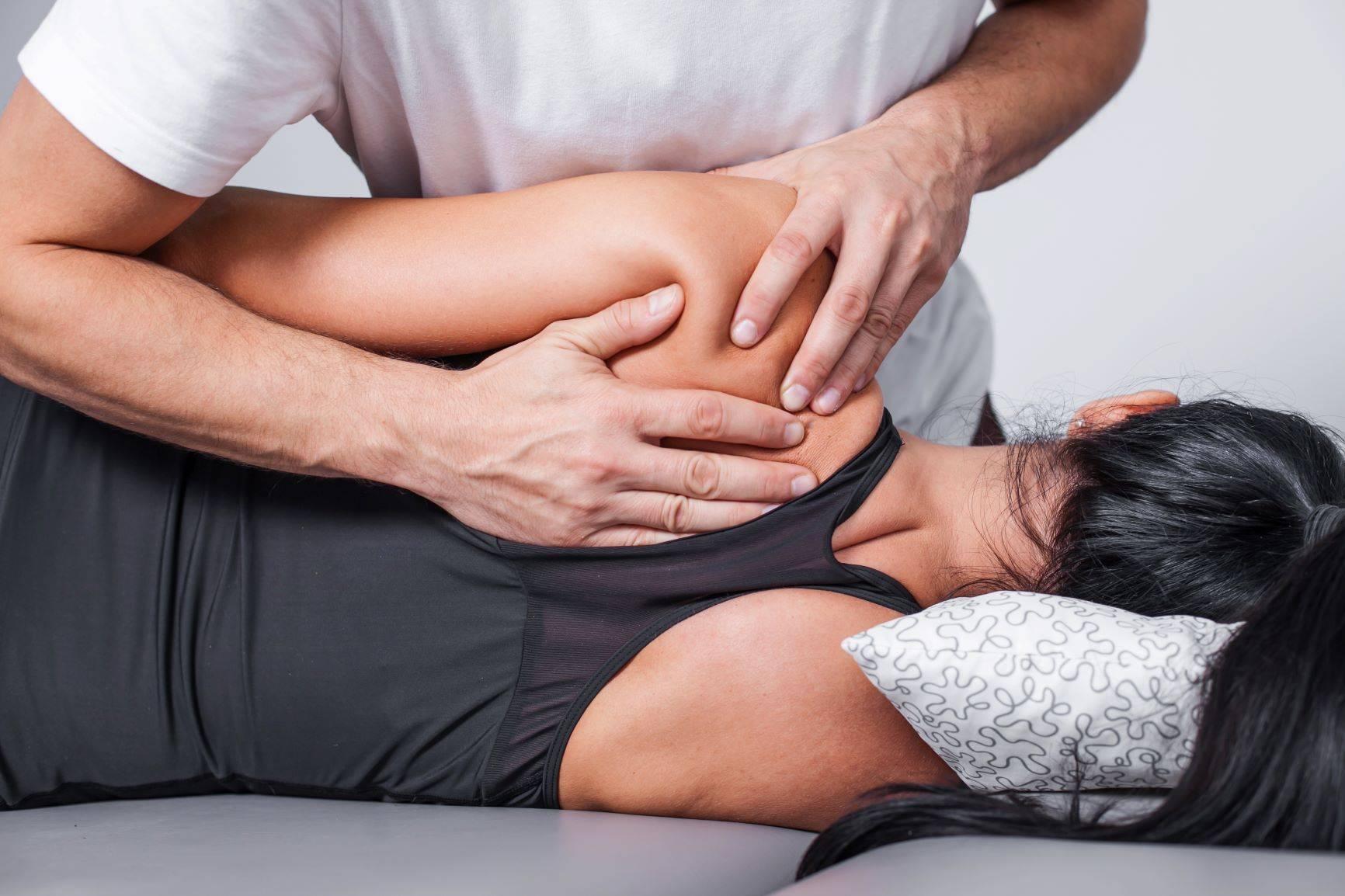 Masaż rolfing - terapia manualna. Fizjoterapeuta wykonuje masaż powięzi kobiety.