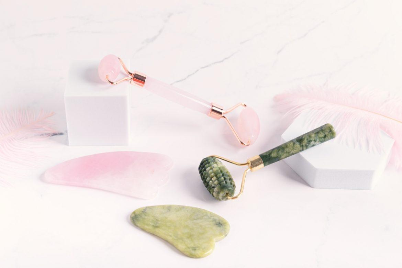 Zimno dla urody: masaż lodem, roller jadeitowy, kamień gua sha, kosmetyki z lodówki, kriolipoliza. Modne akcesoria do twarzy: roller jadeitowy i kwarcowy oraz kamienie gua sha leżą na białym blacie.