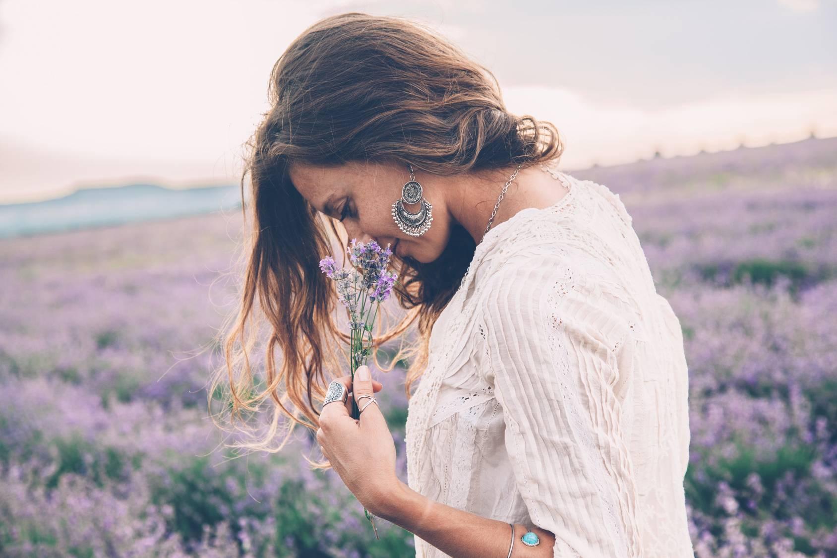 Jak walczyć z depresją wg zasad tradycyjnej medycyny chińskiej? Atrakcyjna kobieta w białej zwiewnej letniej sukience i długich kolczykach spaceruje po łące i wącha zerwany bukiecik fioletowych kwiatów.