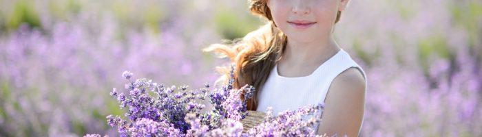Rośliny odstraszające owady: komary, muchy, osy, pszczoły, mole. Dziewczynka trzyma bukiet zebranej lawendy na polu lawendowym.