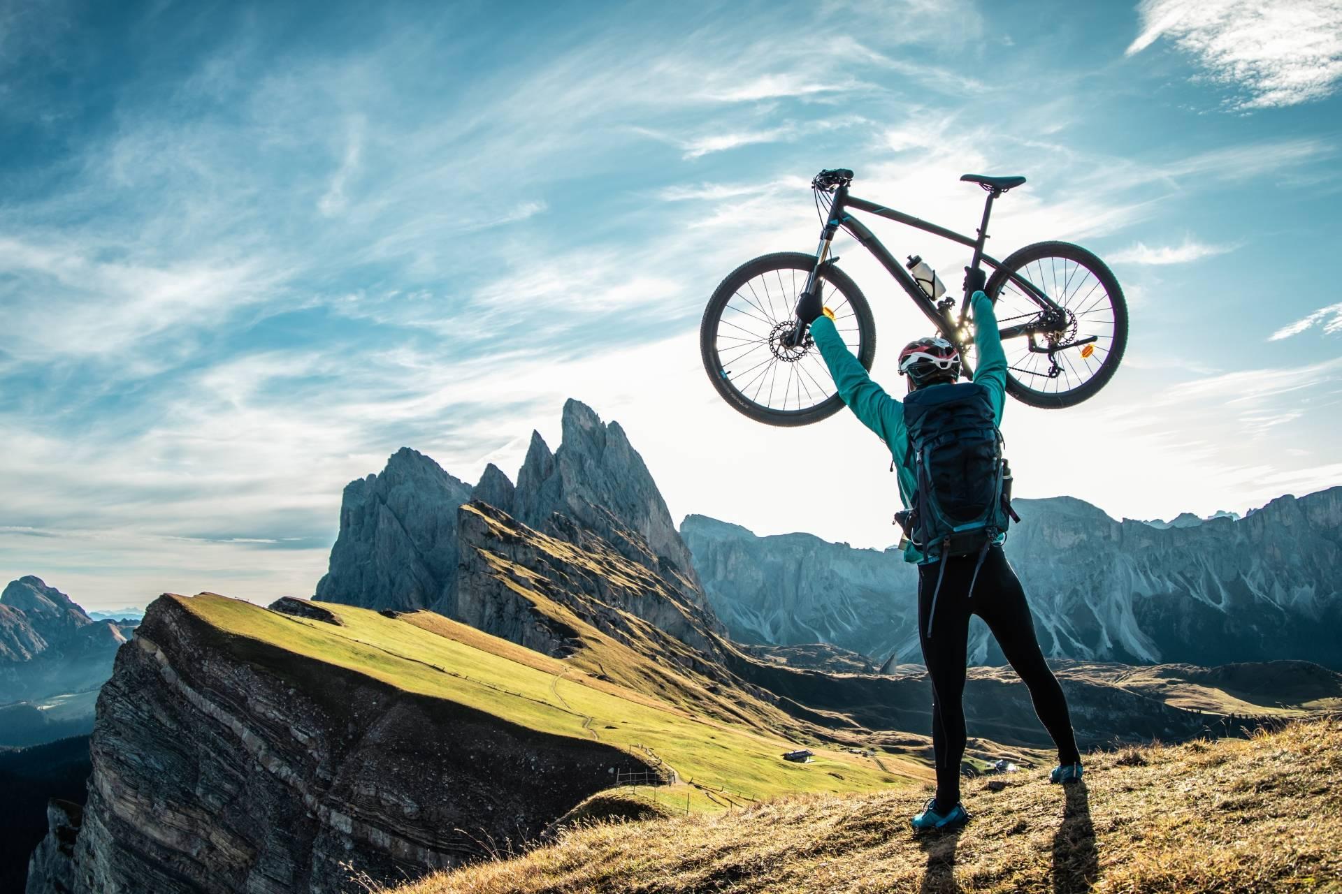Jak znaleźć równowagę między pracą a życiem osobistym? Mężczyzna jeżdżący po górach podnosi swój rower górski w rękach do nieba.