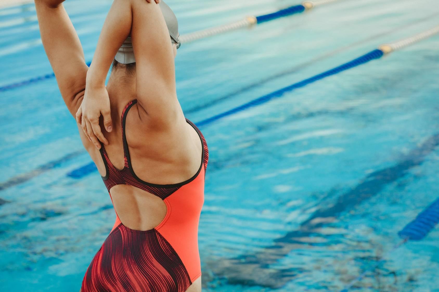 Rozgrzewka przed pływaniem. Kobieta rozciąga się przed skokiem do basenu.