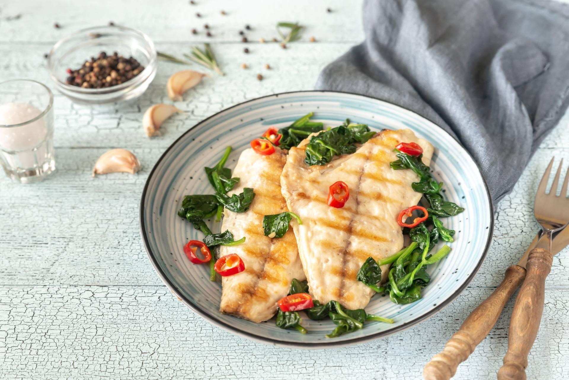 Jaka ryba na obiad - Poradnik rybny WWF podpowie jak kupować ryby odpowiedzialnie. Grillowana ryba saute z warzywami na błękitnym talerzu leży na drewnianym blacie.