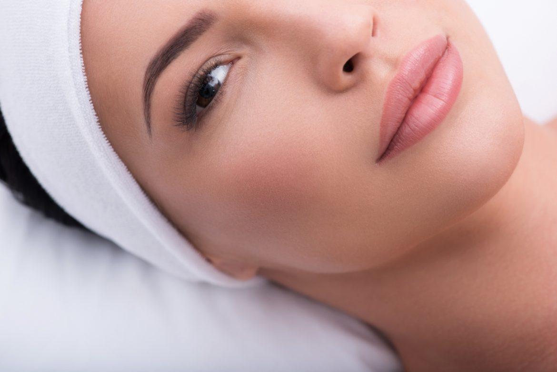 Naturalne sposoby na gęste rzęsy - jak wzmocnić rzęsy? Kobieta o gęstych rzęsach z białą opaską na włosach leży na łóżku w gabinecie kosmetycznym.