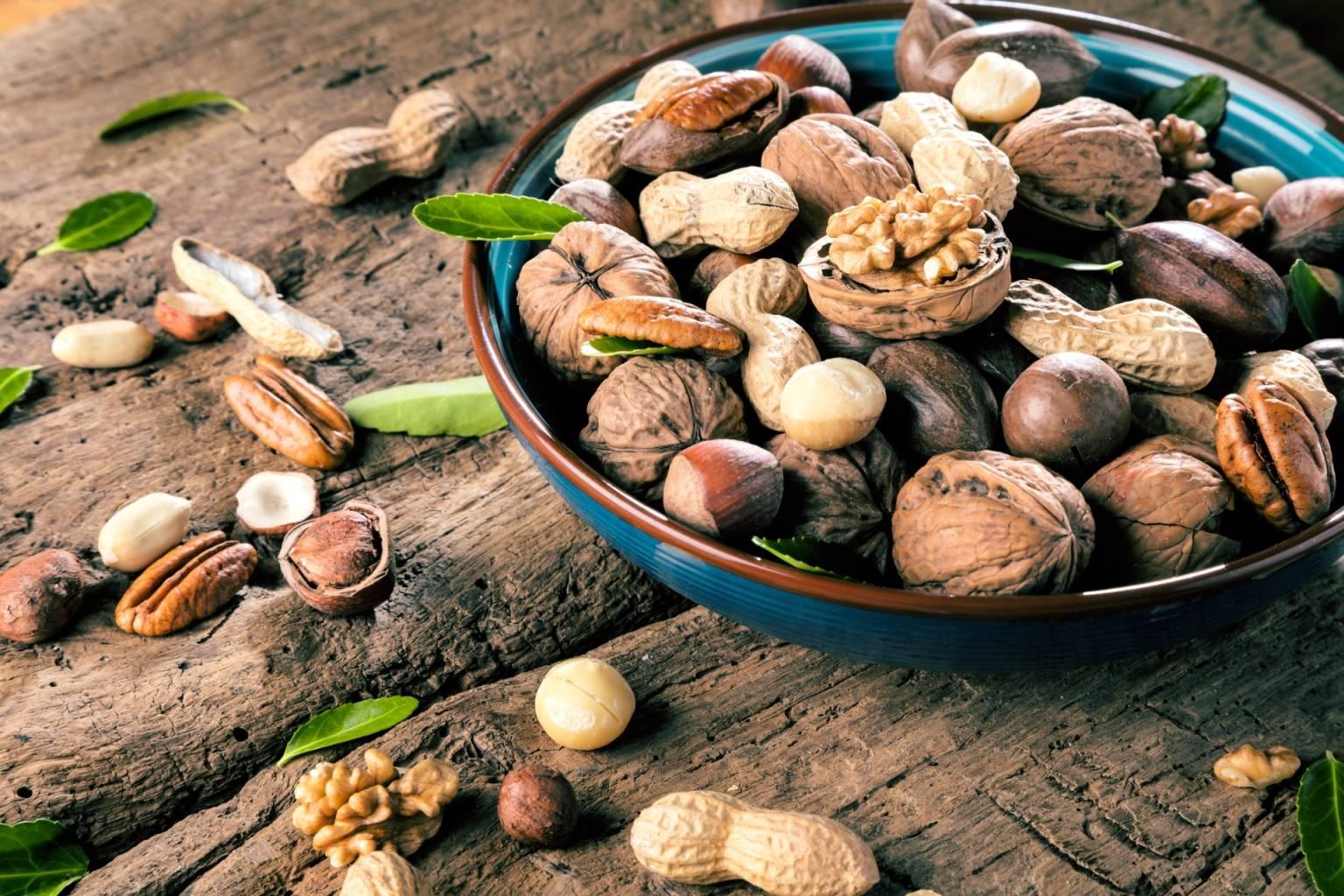 Orzechy włoskie, laskowe, ziemne w niebieskiej misce na starym drewnianym stole. Na czym polega wegetarianizm i jakie ma odmiany?