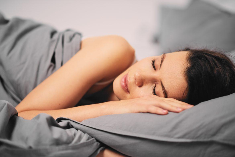 Fazy snu - jak wpływają na jego jakość? Jak zadbać o dobry sen? Kobieta śpiąca w łóżku w szarej pościeli.
