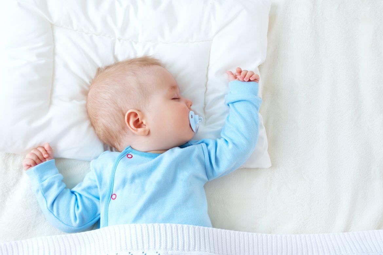 Sen niemowlaka - ile śpi niemowlę? Niemowlak w błękitnym body śpi ze smoczkiem w buzi w białej pościeli.