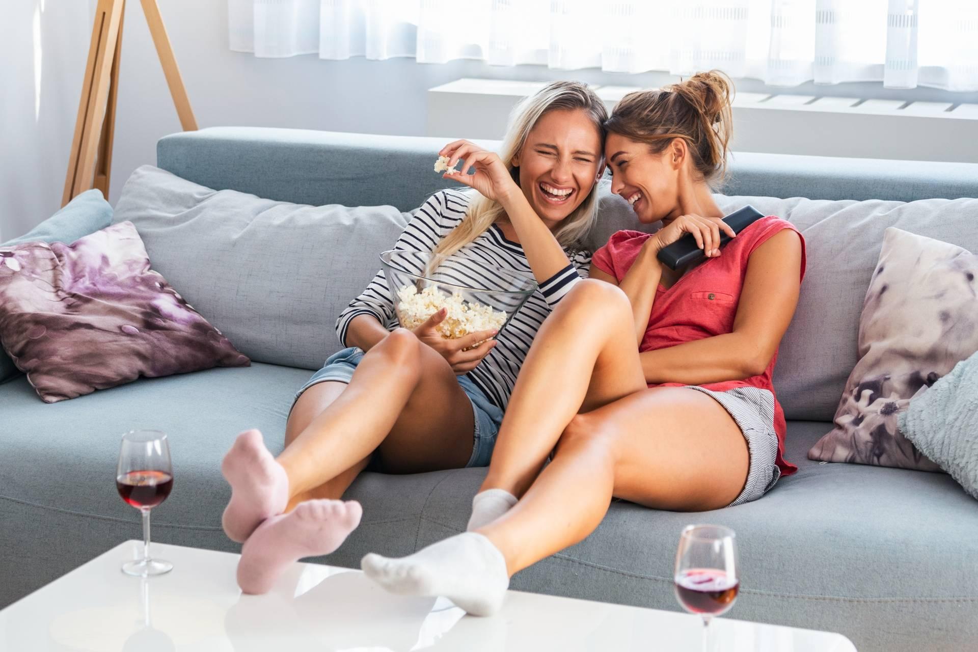Kobiece seriale na poprawę nastroju. Dwie przyjaciółki siedzą na kanapie, śmieją się i oglądają serial.