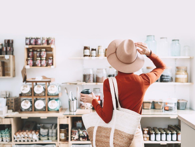Jak żyć w duchu zero waste? Kobieta w eko sklepie wybiera produkty pochodzące ze zrównoważonego rozwoju.