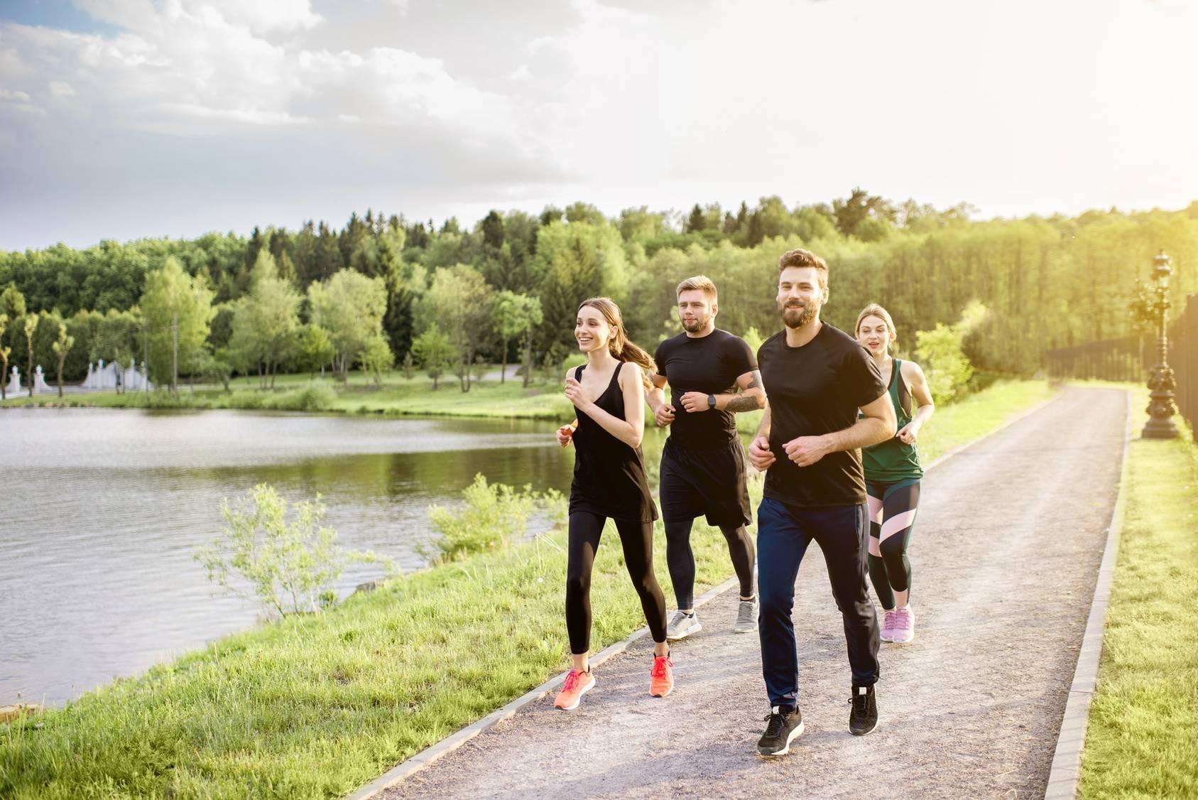 Grupa młodych ludzi uprawia slow jogging na świeżym powietrzu.