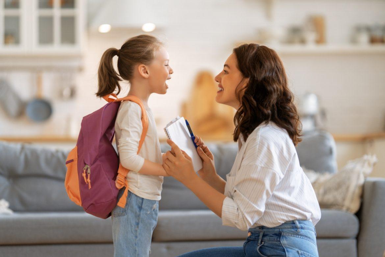 Jak budować poczucie własnej wartości u dzieci? Słowa, które pomogą wzmocnić poczucie własnej wartości u dziecka. Mama rozmawia z córką w salonie przed wyjściem do szkoły.