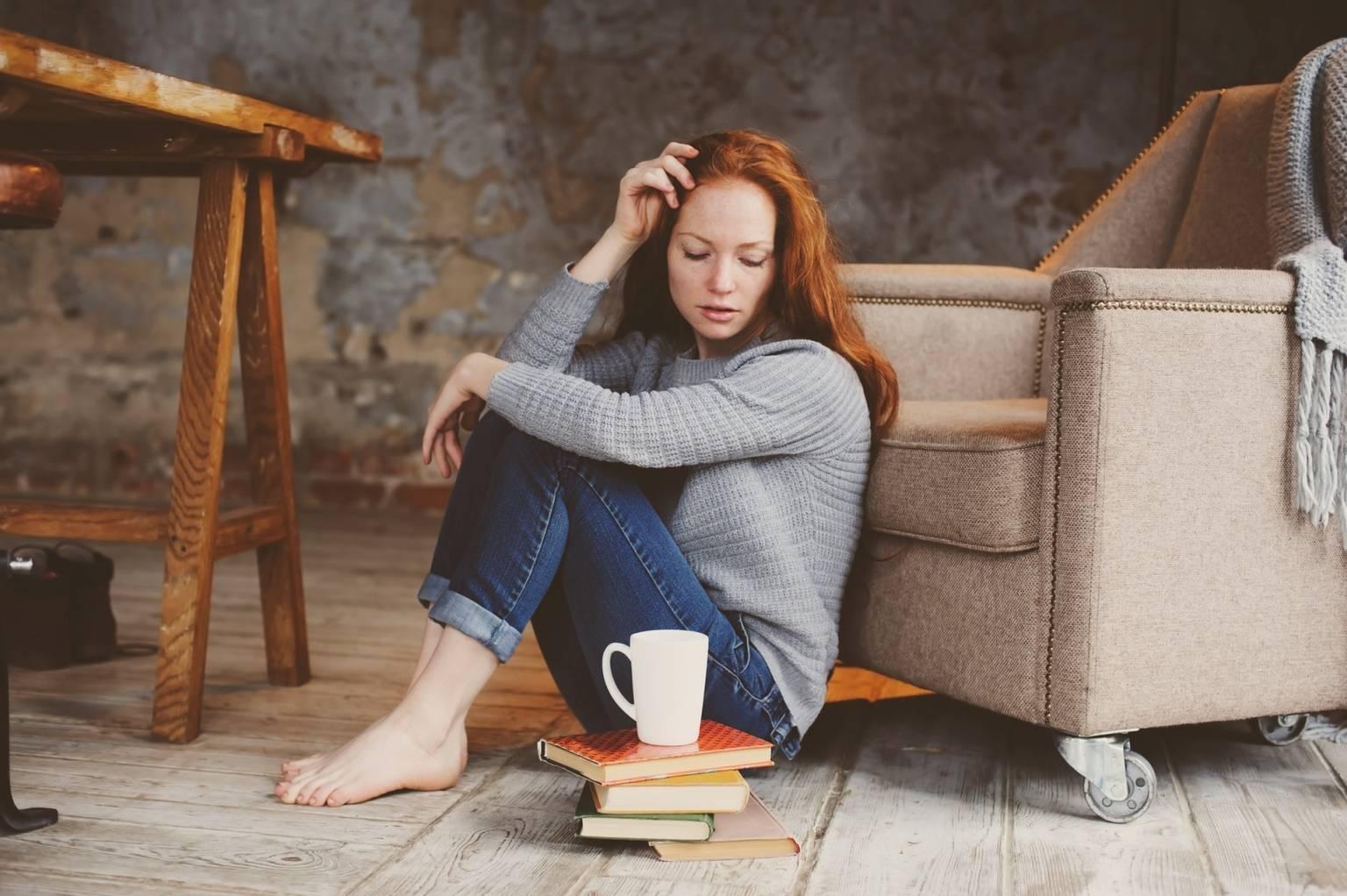 Jak leczyć depresję wg medycyny chińskiej? Rudowłosa zamyślona dziewczyna w szarym swetrze i dżinsach siedzi w pokoju na podłodze, opiera się plecami o fotel, patrzy na kubek herbaty i książki.