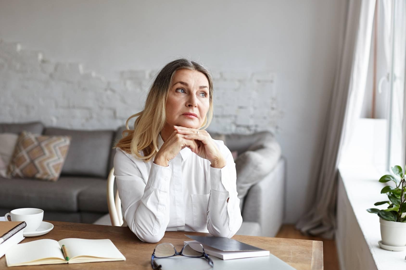 Jakie są sposoby radzenia dobie z zaburzonym shen serca wg medycyny chińskiej? Zamyślona starsza kobieta w białej koszuli wygląda przez okno, siedząc przy biurku.