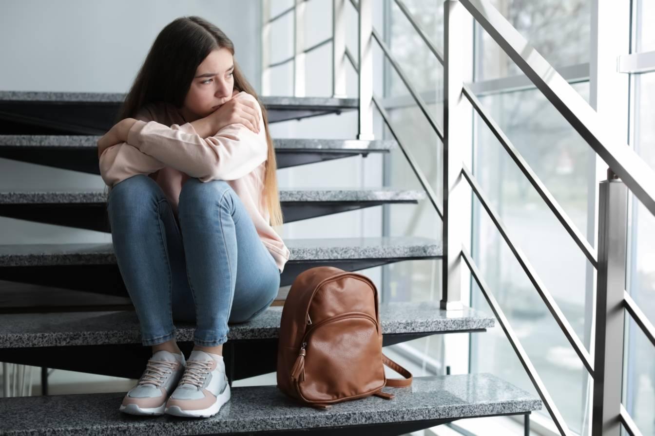Jak pomóc dzieciom z problemami depresyjnymi i lękowymi? Smutna nastolatka siedzi na schodach na klatce schodowej.