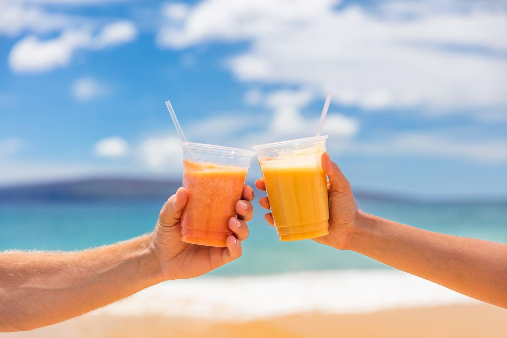 Beta-karoten - para wznosi toast sokiem marchewkowym, wypoczywając na plaży