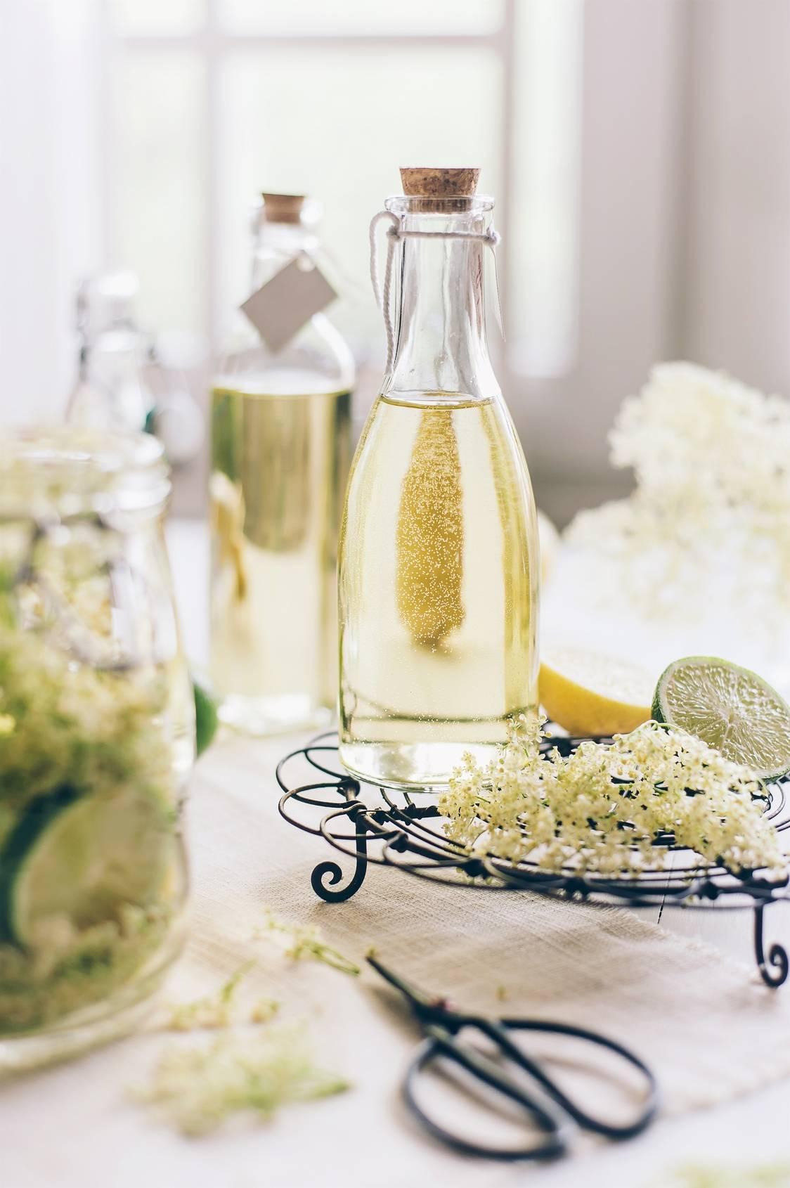 Zioła na obniżenie gorączki. Butelka z sokiem z kwiatów czarnego bzu stoi na stole. Wokół stoją inne butelki i słoiki z przetworami z czarnego bzu, kwiaty czarnego bzu, cytryna i limonka, zdobione nożyczki i druciana tacka.