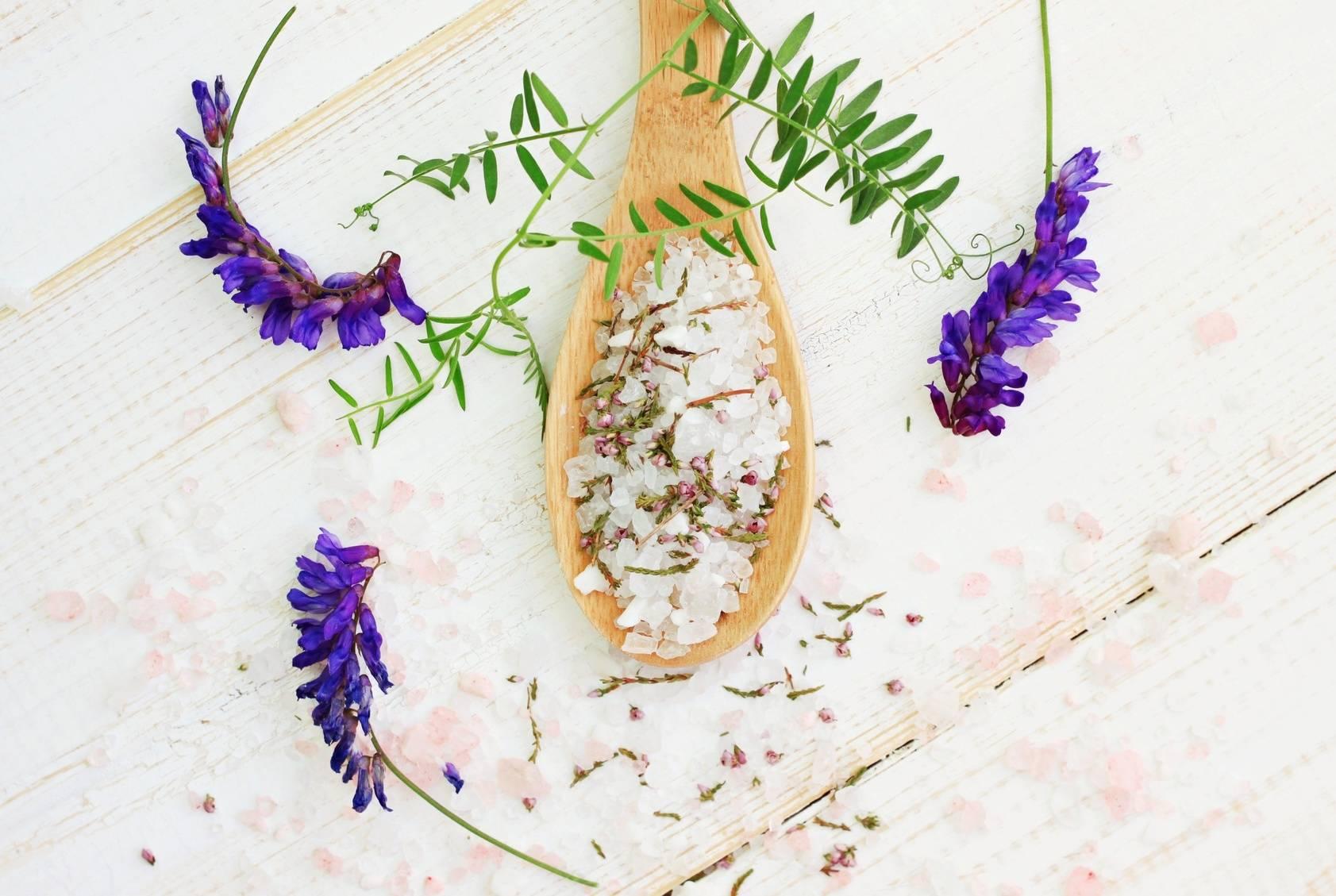 Sól gorzka, sól Epsom do kąpieli i roztworów. 5 sposobów na wykorzystanie soli Epsom. Gruboziarnista sól na drewnianej łyżce, obok leżą liście i fioletowe kwiaty.