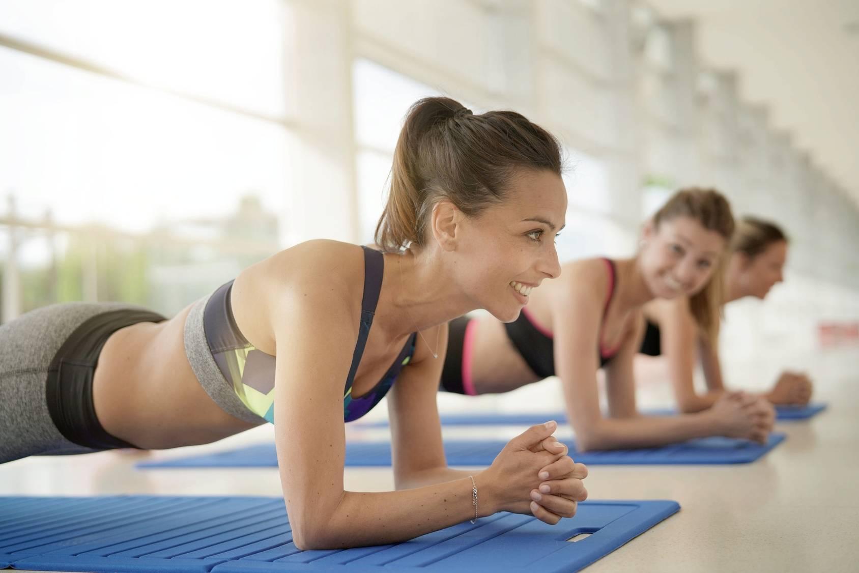 Powięź - jak o nią zadbać, aby zawsze być w dobrej formie? Młode kobiety trenują deskę na sali treningowej.