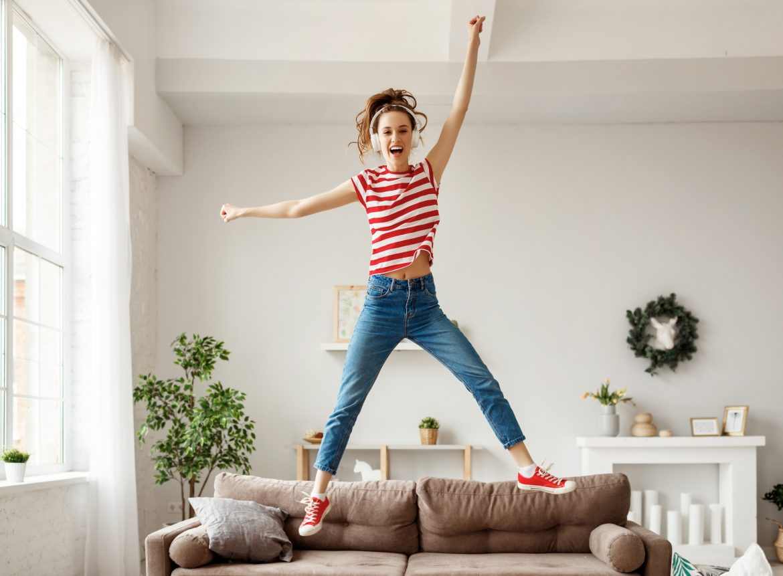 Sposoby na dobry nastrój. Młoda dziewczyna w bluzce w czerwono-białe paski, dżinsach i czerwonych trampkach i słuchawkach na uszach, skacze na kanapie w salonie.