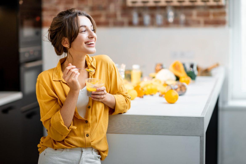 10 sposobów na utrzymanie prawidłowego poziomu glutationu w organizmie. Młoda kobieta z żółtej bluzce je pudding z chia, opierając się o blat kuchenny.