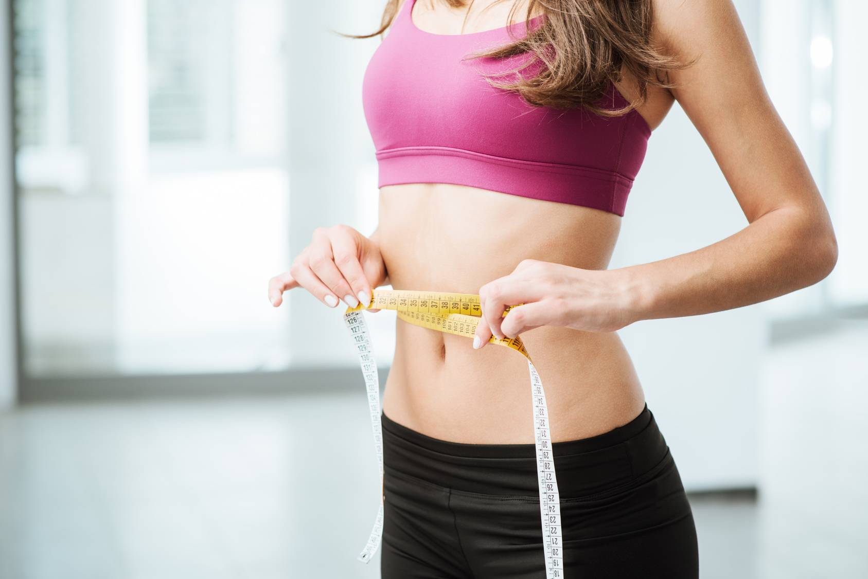 Najlepsze sposoby i ćwiczenia na płaski brzuch. Kobieta mierzy obwód swojej talii.