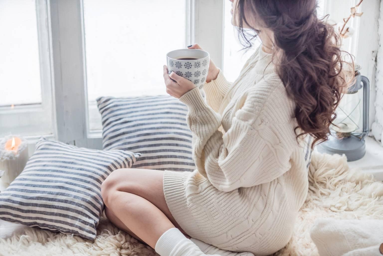 Najlepsze sposoby na przeziębienie. Kobieta ubrana w gruby jasny sweter siedzi na kocu zwrócona przodem do okna i wygląda przez nie. W ręku trzyma kubek herbaty. Sceneria zimowa.
