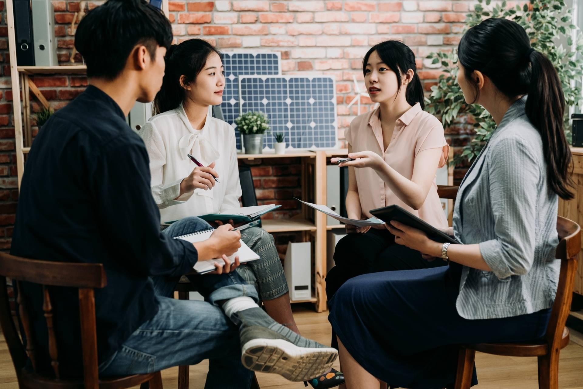 Nunchi - na czym polega koreańska recepta na sukces? Grupa ubranych casualowo współpracowników omawia projekt w biurze.