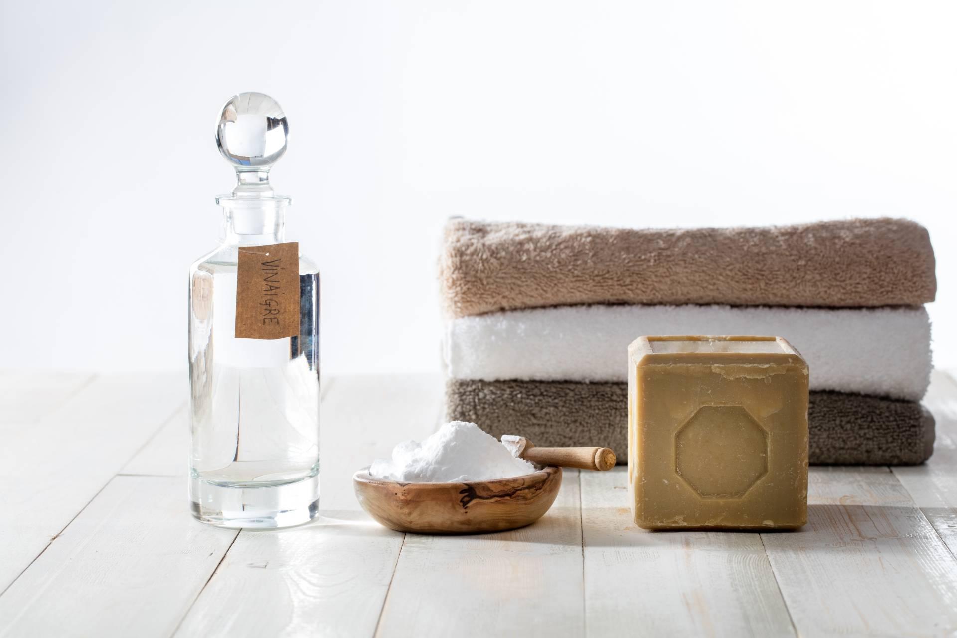 Jak zrobić ekologiczny płyn do płukania tkanin? Butelka octu, miseczka z sodą oczyszczoną, mydło leżą na drewnianej podłodze - w tle ręczniki.