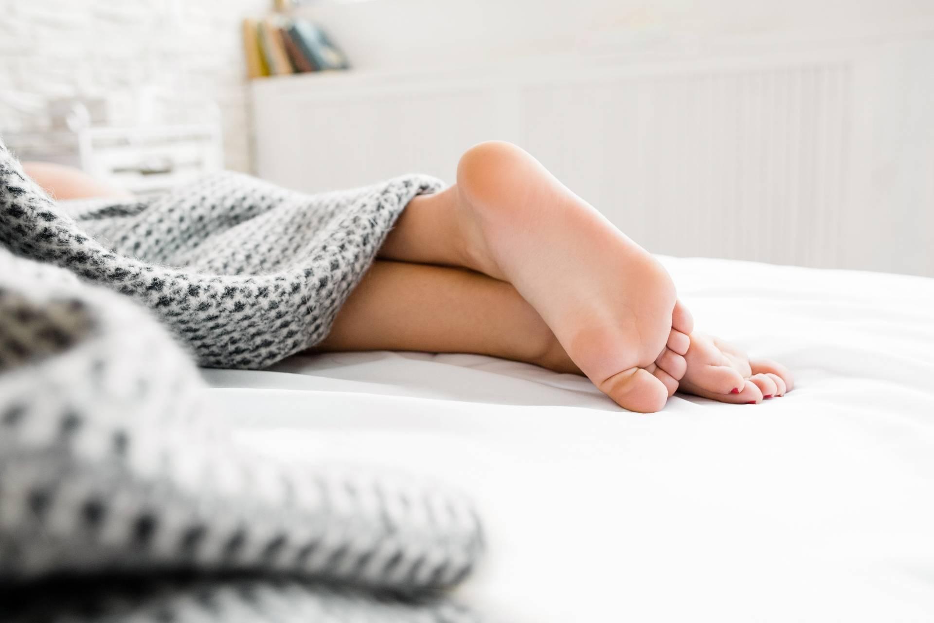 Pękające pięty - jakie są domowe sposoby na popękane pięty? Zbliżenie na kobiece stopy wystające spod kołdry.