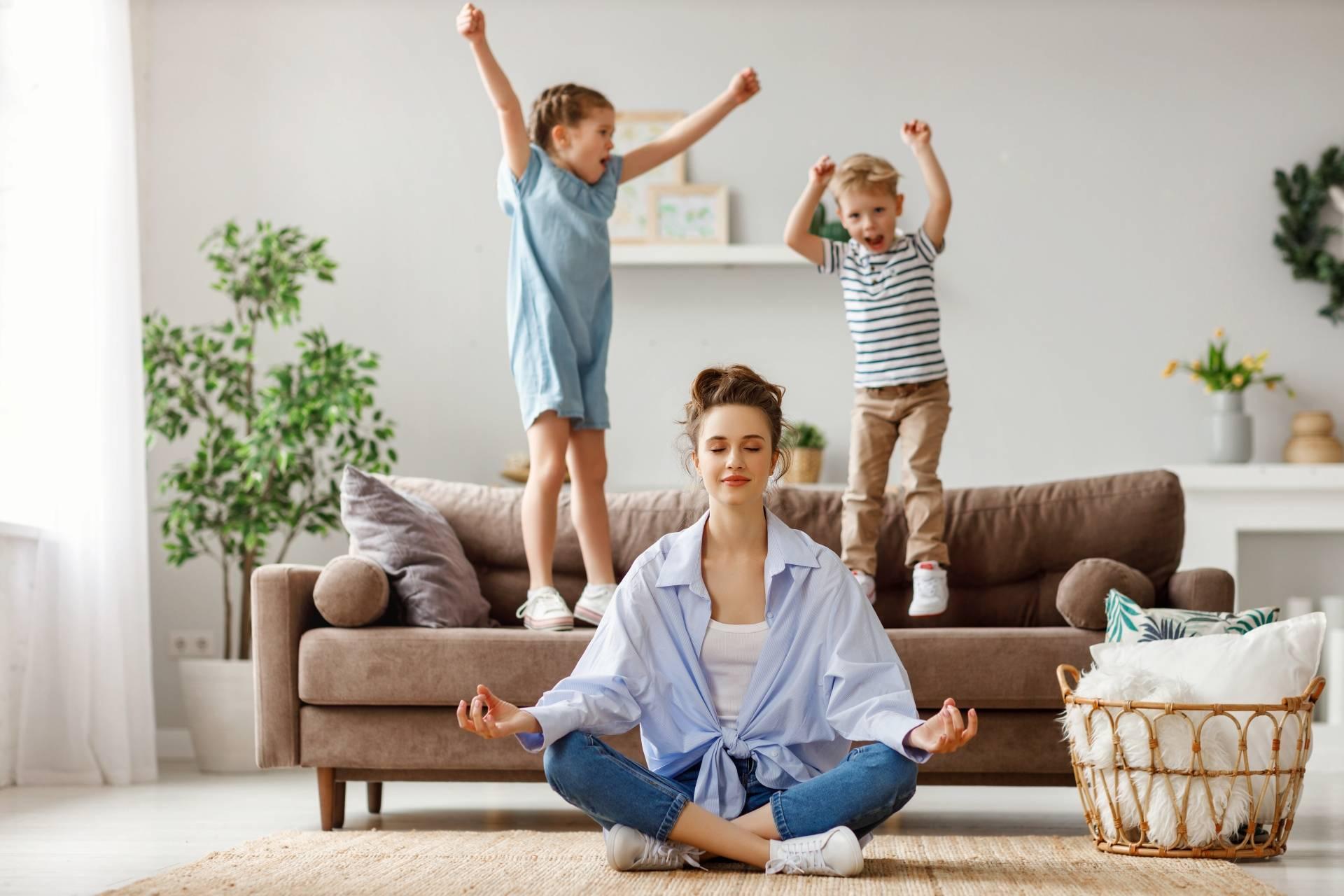 Work-life balance - jak odnaleźć równowagę? Młoda mama siedzi po turecku na podłodze w salonie i medytuje. Za nią na kanapie skaczą dzieci, obok stoi wiklinowy kosz z kocami i poduszką.