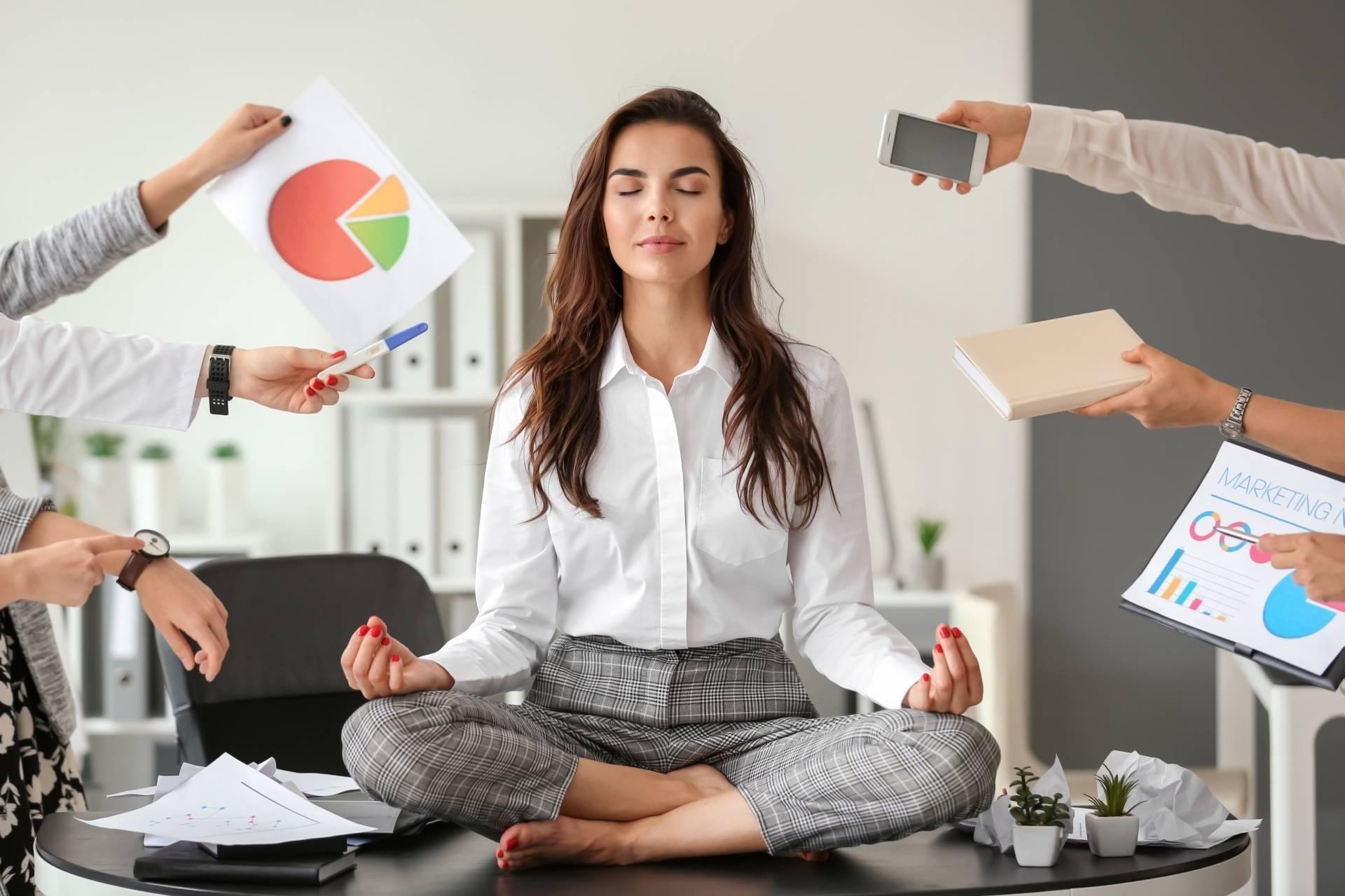 Work-life balance - jak go odnaleźć? Młoda kobieta, pracowniczka korporacji, ubrana w białą koszulę i szare materiałowe spodnie siedzi na biurku, medytuje. Pozostali pracownicy wyciągają w jej stronę ręce z notatkami i rzeczami do zrobienia.