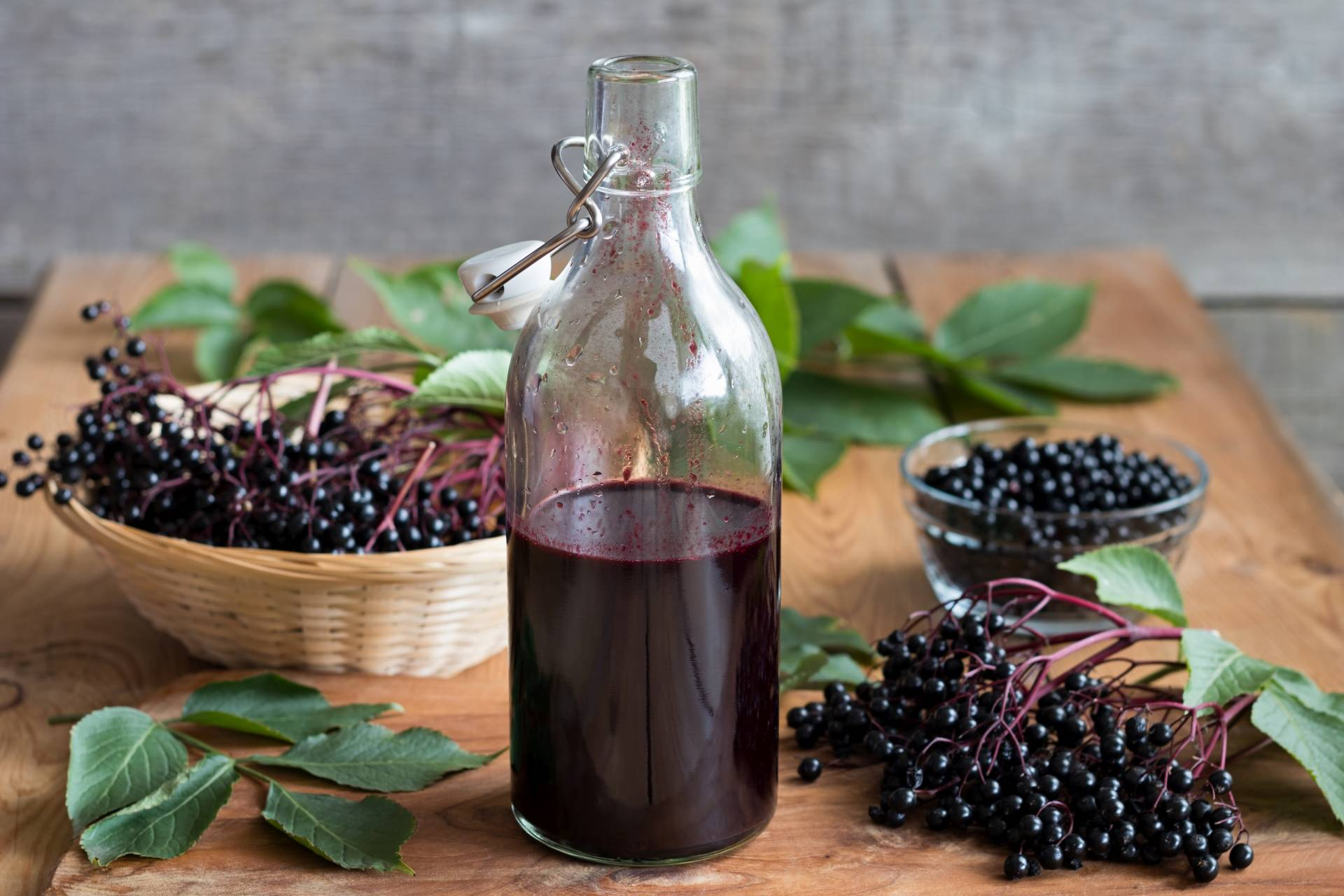 Przepis na sok z czarnego bzu. Butelka z sokiem z owoców czarnego bzu stoi na drewnianym stole. Obok leży koszyk wiklinowy i szklana miseczka z owocami czarnego bzu, wokół rozrzucone liście i łodygi z owocami.