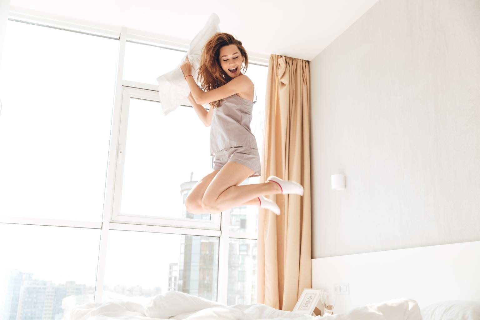 Domowe sposoby na zaparcia. Młoda dziewczyna ubrana w krótkie spodenki, top i skarpetki skacze po łóżku z poduszką w ręku.
