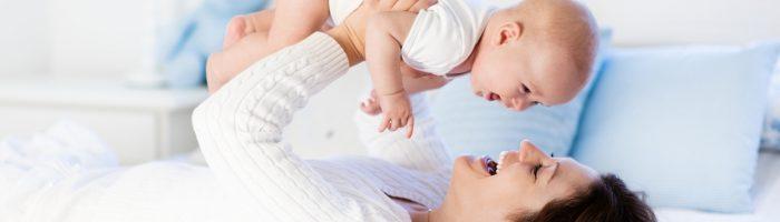Jak zadbać o siebie po porodzie według wskazówek tradycyjnej medycyny chińskiej? Mama bawi się z niemowlęciem na łóżku.