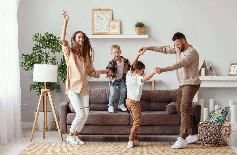 Jak pomóc dziecku rozładować emocje? Felieton Beaty Sadowskiej. Szczęśliwa rodzina - mama, tata i dwójka dzieci w wieku wczesnoszkolnym - tańczy w salonie.