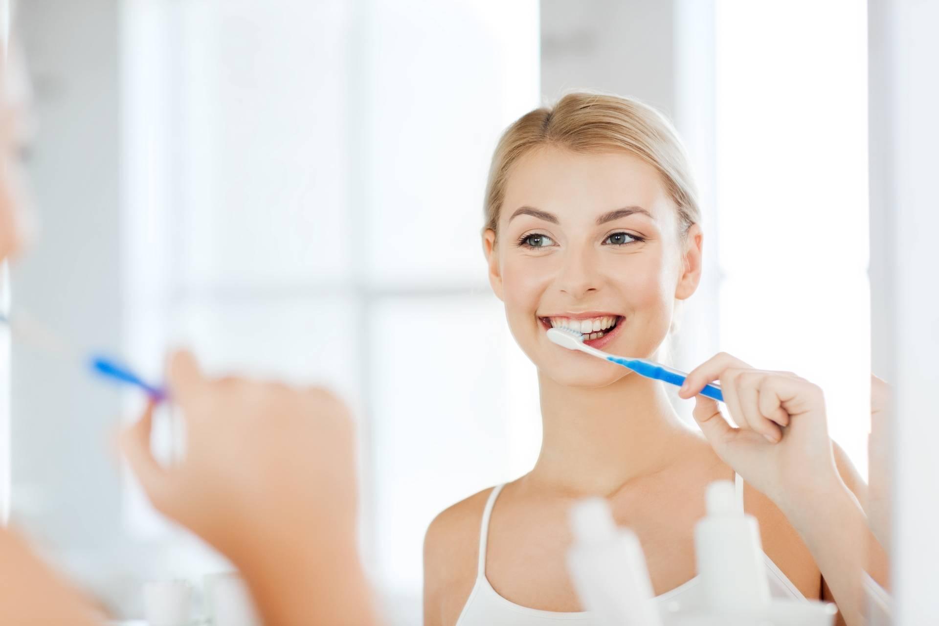 Naturalne sposoby na pleśniawki u dorosłych - leczenie i zapobieganie. Kobieta myje zęby i dba o higienę jamy ustnej.
