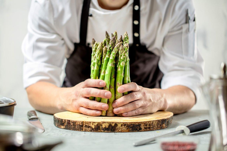 Przepisy na szparagi. Szef kuchni trzyma pęczek szparagów tuż przed pokrojeniem ich na desce.