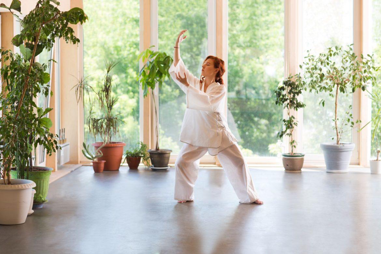 Tai chi - medytacja w ruchu. Kobieta praktykuje tai chi w domu w otoczeniu roślin.